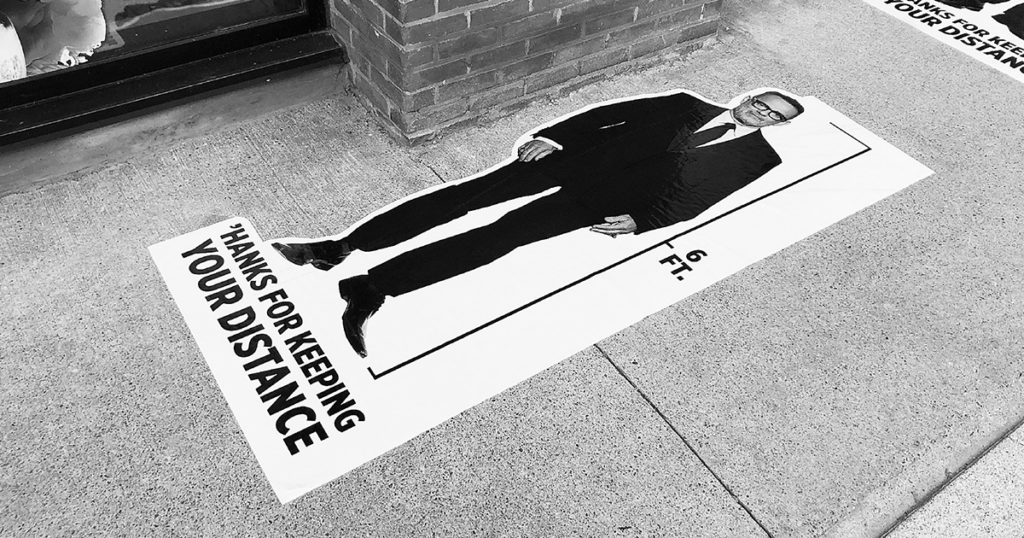 6-feet long decal sticker stuck flat on the ground with image of Tom Hanks standing and text 'Hanks for keeping your distance'